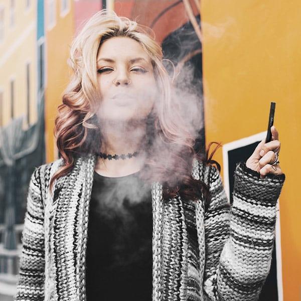 Bud Lab woman enjoying her vape pen in a cardigan