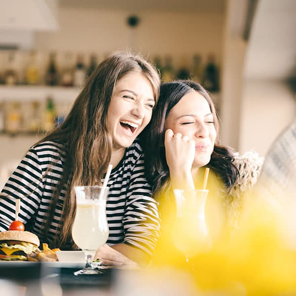 Two Girl Friends Laughing Together
